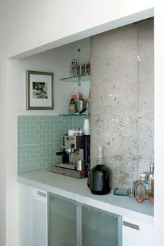 An awkward corner in the hallway is transformed into a nifty bar with glass cabinetry and teal tiles in a Chicago flat.  Photo by: Matthew Williams