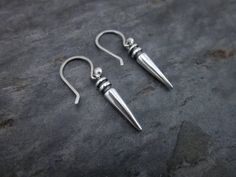 A simple tribal silver spike hangs from my hand made hook earrings. Industrial meets tribal charm...Tumbled to a durable shine, these lovelies