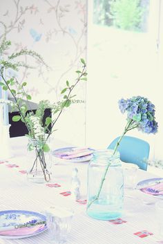 Using a string of flags for table decor for 17.Mai with blue and white dishes and flowers.