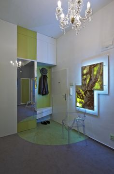Vstupní hala je navržena ve stejných barvách jako koupelna, v kombinaci zelené a šedé. Je doplněna plastovou židlí od značky Kartell. Chloubou je nástěnné dekorativní světlo, podsvícený onyx v nerezovém subtilním rámu.