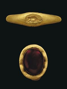 My birthstone. What I would give just to see this piece.... FOUR SMALL ROMAN GOLD RINGS CIRCA 1ST CENTURY B.C.-2ND CENTURY A.D. One with plain hoop widening to an oval bezel with applied phallus; another with bezel with incised figure of a mouse, both circa 2nd Century A.D.; another with high banded bezel with pale green glass inlay; and another with flat hoop, oval bezel with later cabochon garnet, both circa 1st Century B.C.- 1st Century A.D. 5/8 in. (1.5 cm.) wide max.