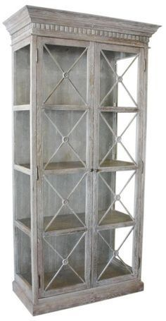 a white washed french style display cabinet featuring glass doors with an x design it