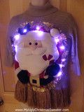 Tacky holiday sweater with huge puffy 3D Santa surrounded in 10 bright lights! Santa is trimmed in garland. This is...