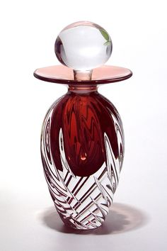 """Grace"" Perfume Bottle by Michael Trimpol   evokes bygone eras and halcyon days gone by. This masterfully cut item of art glass is 16cm tall and will look alluring on a French Dresser or Mantel. Copper and Ruby colors are combined and the cut facets of the glass give these vintage perfume bottles a brilliant luster."