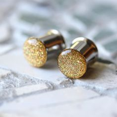 Beautiful sparkly gold ear gauges in custom sizes from 4g up to 2 inches! Hypoallergenic surgical steel tunnels and jewelry grade resin. Handcrafted by Silver Peak Plugs www.silverpeakplugs.etsy.com