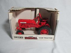 Farmall cub tractor toy in 1:16 scale model in its original box is from Ertl toys of Iowa, USA. Stock #235 from their McCormick Farmall Vintge Series in 1990. It has steerable front end, rubbertires, rear hitch and is made of highly detailed die cast metal.