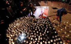 People lay candles as a picture of retired swimming gold medallist Camille Muffat is reflected on the ground in the southeastern French city of Nice, during a tribute after she died in a helicopter crash in Argentina while filming a reality TV show. (Valery Hache/AFP/Getty Images)