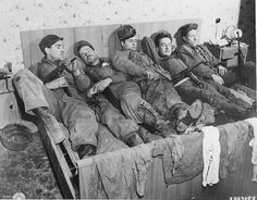 GIs of 69th Division rest after returning from patrol. They settled on a double bed in the bedroom of a house in an unidentified German city.
