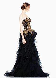 Alexander McQueen. This dress is just stunning with the gold detailing and the black feathery appearance to the skirt.