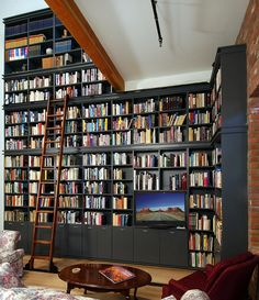 Minimalist Style Home Library with Large Black Wooden Bookcase complete with the Stair and Comfortable Sofa Furniture also Round Wood table on the Wood Flooring for Small Home Library Design Inspirations in 2014