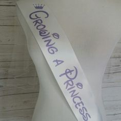 Growing a princess baby shower sash for mom to be to wear. White sash with purple lettering. Fast shipping. Order yours today.
