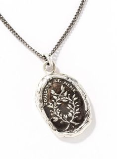 Strung on a delicate sterling silver chain, the sterling pendant is stamped with a laurel wreath, replicating an antique wax seal.