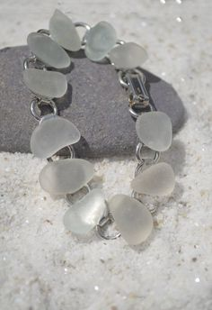 Genuine surf tumbled frosted sea glass chain charm bracelet. Natural frosted sea glass adorns a pretty silver charm bracelet. The sea glass was carefully selected for both its color and shape to make a truly unique and one of a kind piece of jewelry. The bracelet is perfect for a beach wedding or just a date on fun on a hot summer night. The sea glass is frosted beach glass collected on the rocky beaches and coastal shores of Casco Bay, in Maine. The sea glass has a lovely natural frosted…
