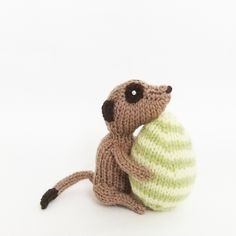 handknitted Meerkat with green and yellow striped knitted Easter egg