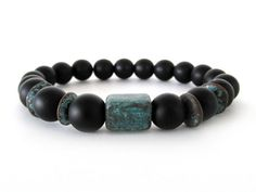 Rugged and masculine men's bracelet with 10mm matte black agate beads and Mykonos ceramic focal/accent beads with a green (turquoise) patina. Thes Greek ceramic beads are hand-formed, kiln-fired with rough copper and then finished with a coating of pure copper and a beautiful patina. Since these beads are so unique, each bracelet will vary slightly from the one shown but will have the same stunning quality and appearance.