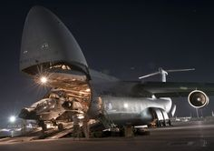 Airmen and soldiers load an AH-64 Apache attack helicopter aboard a C-5B Galaxy transport at Bagram Airfield, Afghanistan, Aug. 31, 2012