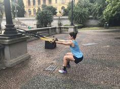Mulher fazendo fazendo um agachamento segurando o TRX no treino de Crossfut