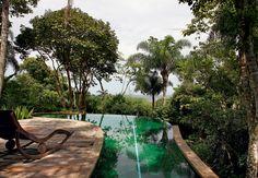 A sensação de que a piscina não termina e se confunde com a mata foi proposital neste projeto assinado pelo arquiteto Ricardo Ferri. À esquerda, cadeira de madeira para relaxar