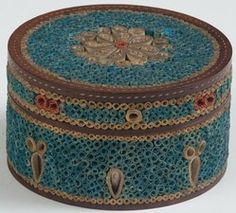 A circa 1780 Regency rolled paper filigree and satinwood inlaid circular box. The cover worked with a red and gold flowerhead on a blue ground and within a ...