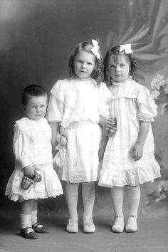 Full portrait of the Cole children, a boy and two girls, who are wearing broderie anglaise and pin-tucked smock dresses with ruffles, shoes with button fastenings and carrying small cane baskets
