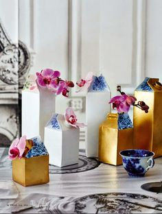 Milk cartons spray painted gold or white and decoupaged with delft-like papers: Cool Decorating Tricks from Ideas Magazine