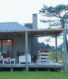 Rodeada de verde y construida en una planta, esta casa en Punta del Este transforma el blanco y la madera en los protagonistas del espacio.