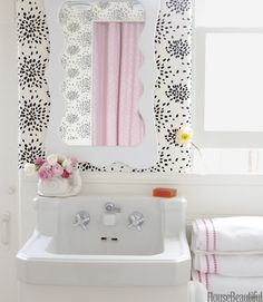 "Polka-Dot Wallpaper  Kristen Ewart designed this tiny California beach house bathroom with Hinson's Fireworks wallpaper by Albert Hadley, a mirror Ewart designed, a light fixture from Old School Lighting, and Pottery Barn towels. ""This polka-dotty print with the pink herringbone shower curtain just makes me happy,"" Ewart says."