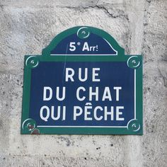 Translation - A cat with a fish. It is one of the most narrow, small streets in Paris