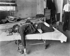 The dead body of Walter Sage.Sage was a New York racketeer who ran afoul of the mob. He was hacked to death with an ice pick, tied up to a slot machine, and left out in public as a warning.New York City.