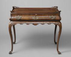 Anonymous   Tea table, Anonymous, c. 1750 - c. 1775   Mahoniehouten theetafel. De vier gestrekt S-vormige poten met bal en klauw lopen over in de tafelregel. Op de zwellingen is een schildvormige versiering aangebracht. De uitgezaagde tafelregel is aan de onderzijde afgezet met een aaneenschakeling van geprofileerde gestrekte S-motieven. De ruimte met de lade is gebombeerd. De lade heeft een symmetrisch uitgezaagde koperen slotplaat en twee gelijkvormige trekkers. Het blad heeft een…