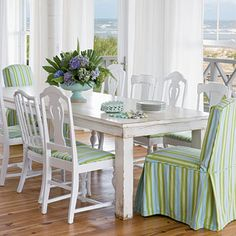 Fun seaside umbrella stripes in green and aqua add life to this country style table and chairs in a beach cottage dining space with an ocean view...