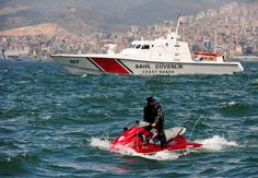 checking out the crowd - a coat guard boat and a policeman on a waverunner checking out the crowds from the sea during labor day rally in izmir