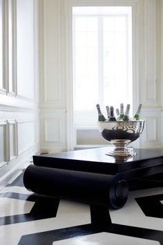 Ralph Lauren Home's Brook Street Cocktail Table, a low, black coffee table with dramatically scaled pillar legs