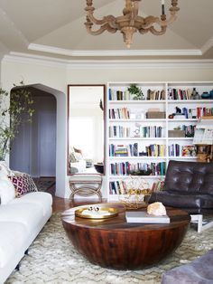 Eclectic living space with giant bookshelf, antique chandelier, and midcentury leather chair