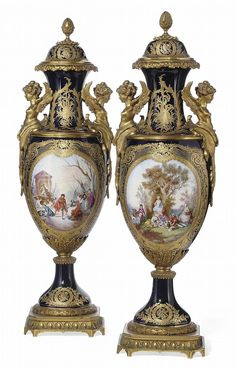 A PAIR OF SEVRES-STYLE GILT-METAL-MOUNTED BLUE-GROUND VASES AND COVERS <br />CIRCA 1900, BLUE INTERLACED L'S MARKS <br />Of slender ovoid form, gilt-metal-mounted with winged female bust handles, each painted and indistinctly signed with a gilt-framed panel enclosing a winter scene of skaters on a lake or a summer scene of peasants picnicing, the reverse with landscape scenes, all against the dark-blue ground, mounted on a gilt-metal square base with canted corners, the covers with ...