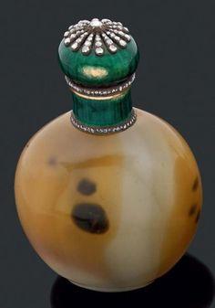 Flacon à parfum en agate orné d'un bouchon en or jaune et argent à décor émaillé vert rehaussé de diamants taillés en roses. Poinçon de maître.