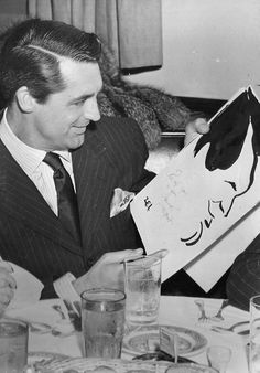 Cary Grant is amused by a caricature presented to him at the Brown Derby, c. 1940.