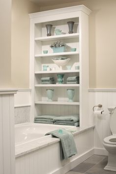 cut the bottom shelf out around the tub frame, then use construction adhesive to seal it in place if going for the built-in look. less expensive version - add a bookcase on the tub @ MyHomeLookBookMyHomeLookBook
