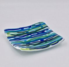 "Dreaming of Seaside, Florida 5"" Fused Glass Square Plate. If you've ever seen the colors of the Gulf of Mexico during a vacation at Seaside, Florida, this dish will take you there again. This is a 5"" square kiln-fired white art glass dish infused with glass stringers and murrini in shades of blue and green. It is a versatile dish that will add a beachy and functional touch in a kitchen or bathroom as a trinket dish to hold rings at the sink, function as a spoon rest at the range, or as a..."