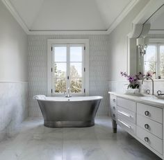 This bathroom's tile floor is echoed on the walls, creating a cohesive look and providing a canvas to showcase a freestanding tub, mosaic tile pattern, and sculptural bath fixtures. Bathroom Floor Tiles, Tile Floor, Marble Floor, Bedroom With Bath, Master Bath, Master Bedroom, Grey Wall Tiles, Cast Iron Tub, Bathroom Accents