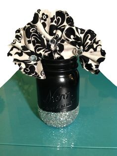 DIY Mason Jar Glitter Vase.   Use an old Mason Jar, black Krylon high Gloss spray paint, glossy Mod Podge glue, silver glitter and a paint sponge.  Spray paint and let dry.  You may apply masking tape around the bottom of the jar to make a straight line.  Do so gently and remove gently.  Apply glue in sections under the tape, while adding glitter along the way.  Do NOT wash.  Enjoy!