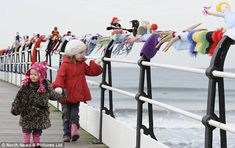 Mystery knitter attaches 50-yard-long scarf featuring woollen athletes to pier