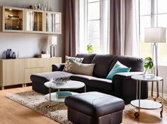 A living room with a dark brown two-seat leather sofa with chaise longue and a footstool. Combined with a round coffee table and storage in white stained oak effect.