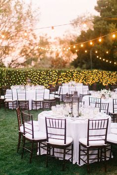 An outdoor wedding reception with string lights | Brides.com