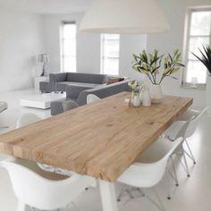 table en bois clair, chaises blanches en plastique, fleurs…