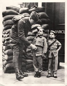 "1939- British soldier goes through the formalities of ""kit inspection"" for small boys beside a sandbag barricade in London. Exact replicas of service uniforms were sold for children in London stores."