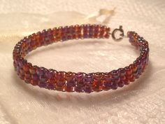 Beaded bracelet - blue and red pattern - handmade from quality Japanese seed beads. Includes cream organza gift bag.