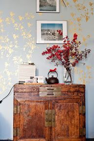 I love the gold stencil on the grey wall--and the patina of the wooden cabinet below.
