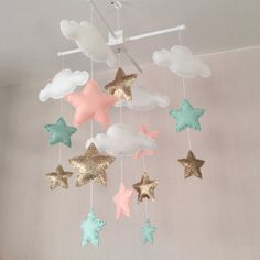 Clouds and stars baby crib mobile. An ideal gift for a new babys nursery or room decor in an older childs bedroom.  This mobile consists of five white clouds and twelve stars (pale coral, mint green and twinkling gold) in three sizes. The elements are suspended with white thread from either a natural wood or a white wooden mobile hanger.  Each element is created with felt or fabric and entirely hand sewn. The clouds and stars are lightly stuffed with hypo-allergenic polyester stuffing. There…