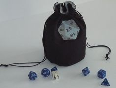 """This pouch has a machine embroidered blue/gray D20 on it. The outer fabric is black with a blue & white lining fabric. This pouch is 6 1/2"""" high, 4"""" round. It will stand open on the game table. It has a black drawstring on 2 sides. Embroidery pattern is from Urban Threads."""